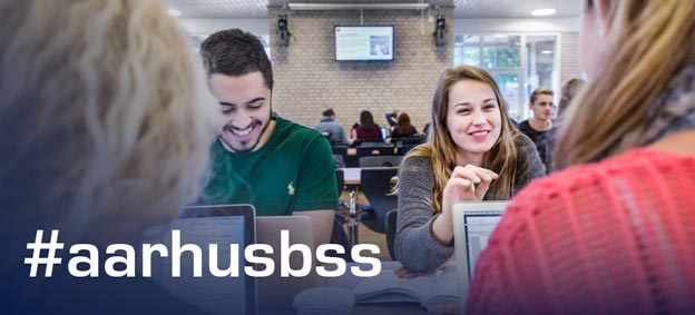 A group of students is seen laughing at a table. The hashtag #aarhusbss covers the left corner of the picture.